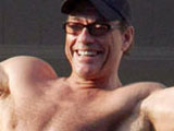 Jean-Claude Van Damme waving to the fans below from his hotel room balcony at the Carlton Palace during the 61st Cannes Film Festival