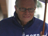 Larry King leaves a FedEx Kinko&#39;s store in the rain Los Angeles, California.