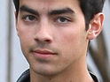 Joe Jonas reportedly buys a hot dog and a cola drink for a girl in the crowd of a basketball game.