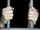 Prisoner holding onto bars