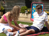 Jodie rubs sun cream onto Darren.