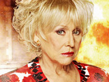 Peggy Mitchell in front of the burning Queen Vic in EastEnders 