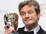 Colin Firth proudly gazing into one of the many BAFTA Film Awards won at the 2011 ceremony