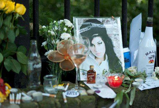Bottles of alcohol, cigarettes and flowers line the wall in Camden Square
