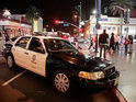 Police close down Hollywood Boulevard as people throw bottles and jump on to police cars outside Grauman's Chinese Theatre.