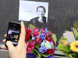 An iPhone is used to take a picture of a shrine at an Apple store in Sydney, Australia.