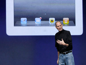 Steve Jobs stands under an image of the iPad 2 at an Apple event at the Yerba Buena Center for the Arts Theater in San Francisco, March 2011