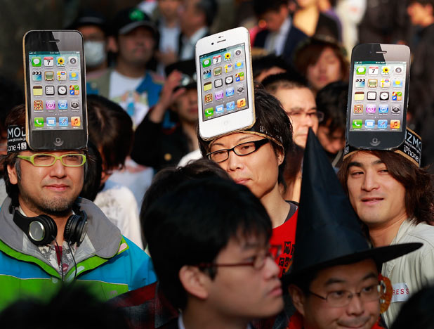 Apple Inc. fans wait in line in front of a shop in Tokyo