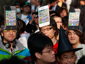 Apple Inc. fans wait in line in front of a shop in Tokyo to buy its new iPhone 4S