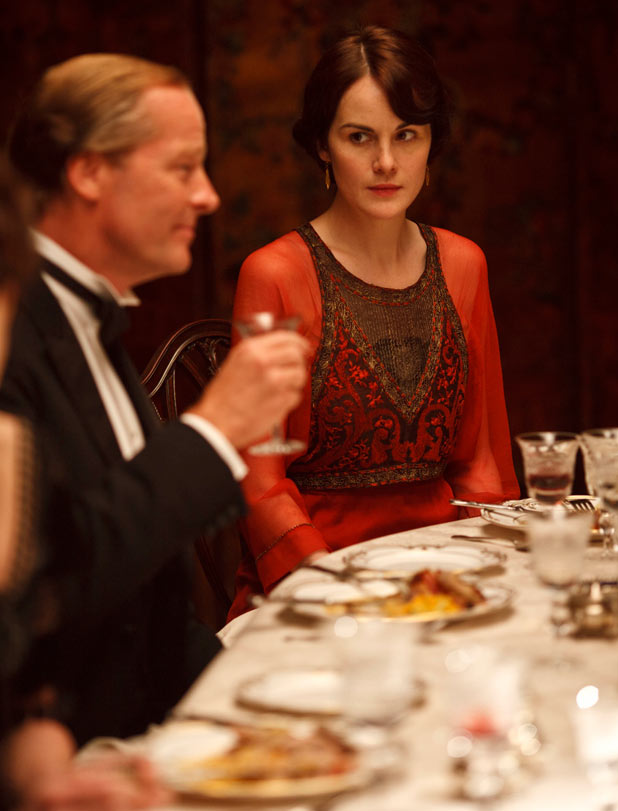 IAIN GLEN as Sir Richard Carlisle and MICHELLE DOCKERY as Mary.