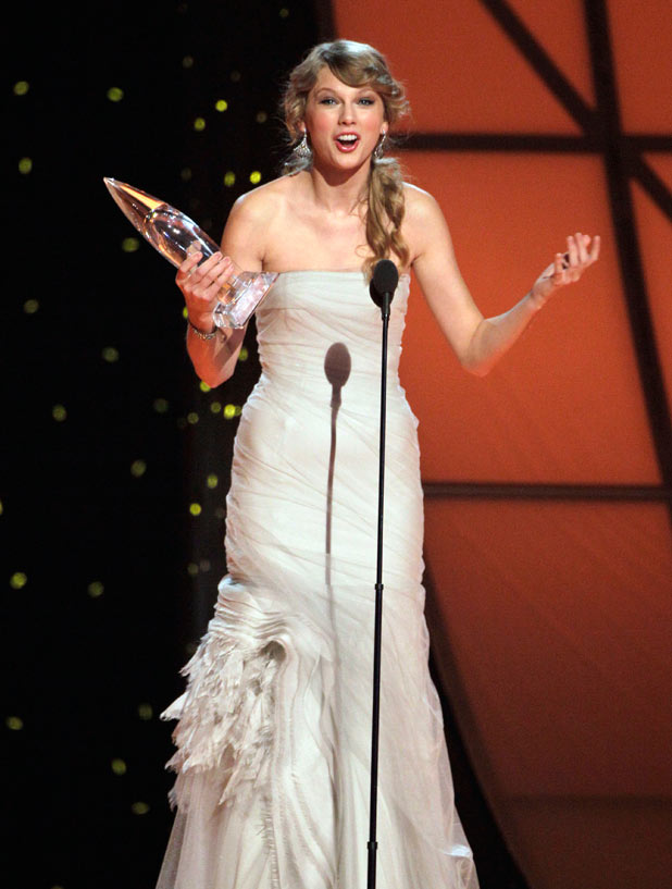 An ecstatic Taylor Swift accepts the coveted 'Entertainer of the Year' trophy for the second time - she previously won the award in 2009.
