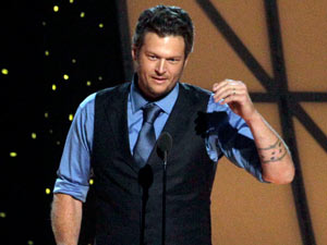 Lambert's husband - The Voice judge Blake Shelton - accepts the award for 'Male Vocalist of the Year'.