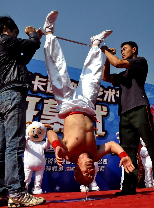 Li Xin performs a headstand on a nail in China