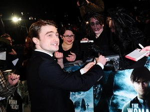 Daniel Radcliffe signs autographs for fans at the world premiere of The Woman in Black, at The Royal Festival Hall