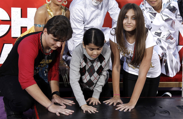Paris, right, Prince, left, and Blanket Jackson put their hands in cement during the hand and footprint ceremony honoring their father, musician Michael Jackson