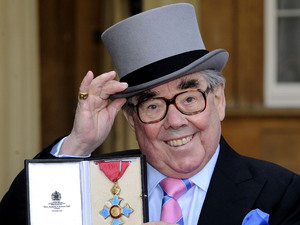 Queen Elizabeth II presents Ronnie Corbett with his Commander of the British Empire (CBE) medal during an Investiture ceremony at Buckingham Palace