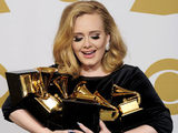 Adele poses backstage with her six awards at the 54th annual Grammy Awards