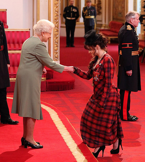 Queen Elizabeth II presents Helena Bonham Carter with her Commander of the British Empire (CBE) medal during an Investiture ceremony at Buckingham Palace