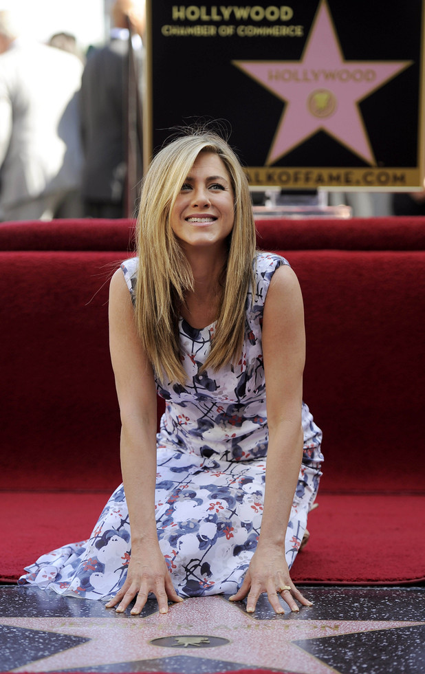 Jennifer Aniston poses atop her new star on the Hollywood Walk of Fame in Los Angeles