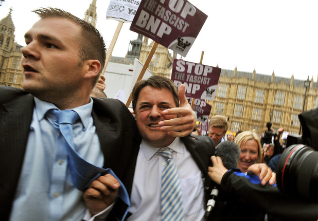 A bodyguard rushes BNP leader Nick Griffin (centre, grey striped tie) to his car as he abandons a press conference outside the Houses of Parliament in London after protesters barracked him and threw eggs.