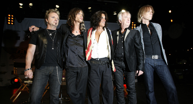 Members of the band Aerosmith pose for the media during a news conference