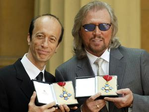 Robin and Barry Gibb hold their CBE's after receiving them from the Prince of Wales at Buckingham Palace, London