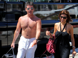 A shirtless ≈and his fiancee, Mezhgan Hussainy, change boats in the port of Nice.  With their friends they leave the 'Slipstream' for their new boat the 'Siren.' Nice, France