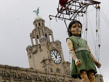 The Little Giant Girl is hoisted into the air outside Liver building, Liverpool.