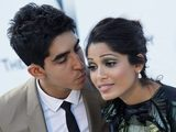 Freida Pinto gets a kiss from boyfriend Dev Patel at the amfAR Cinema Against AIDS benefit in 2011.