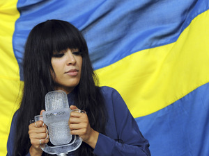 Eurovision Song Contest 2012: Loreen stands in front of Sweden's flag with the winner's trophy.