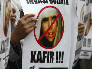 "Protestors hold up pictures of Lady GaGa bearing the words ""Reject cultural invasion"" and ""infidel"" at a protest in Indonesia - May 24, 2012"