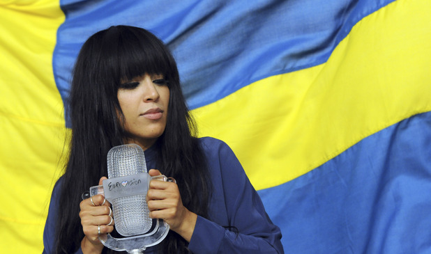 Eurovision Song Contest 2012: Loreen stands in front of Sweden's flag with the winner's trophy