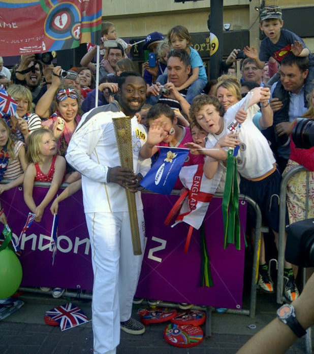 will.i.am carries the Olympic Flame in Taunton, Somerset.