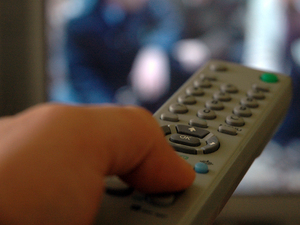 Image of a button being pressed on a TV remote control