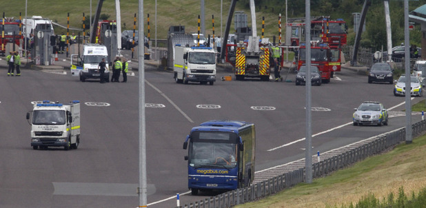"A bomb deposal van drives past a Megabus coach on the M6 toll motorway near Weeford, Staffordshire, after it was shut following a ""police-led incident""."