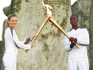 Michael Johnson holds the Olympic Torch at Stonehenge