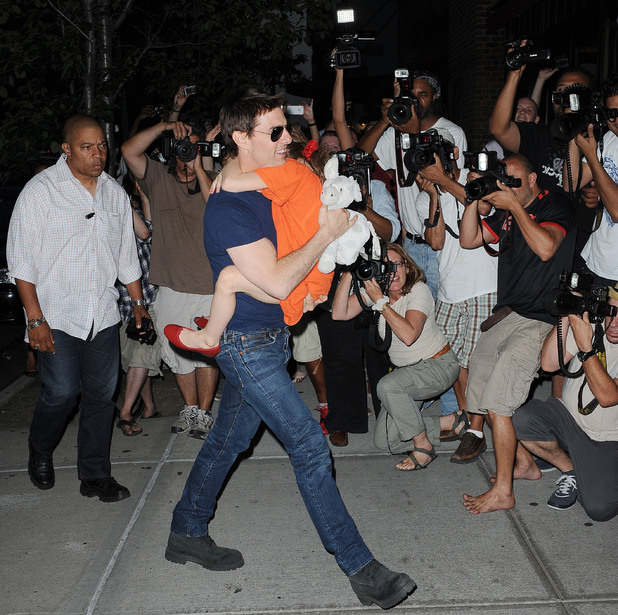 Tom Cruise, with daughter Suri runs a gauntlet of photographers in New York City - July 17, 2012