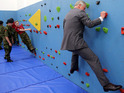 Prince Charles navigates a climbing wall while wearing a suit in Jersey.