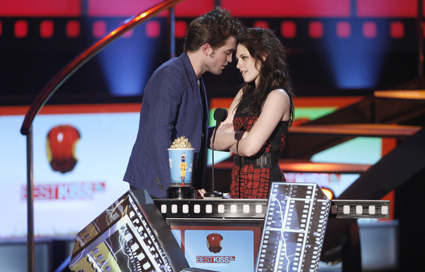 Robert Pattinson and Kristen Stewart get close at the MTV Movie Awards in 2009 as they receive their first best kiss award