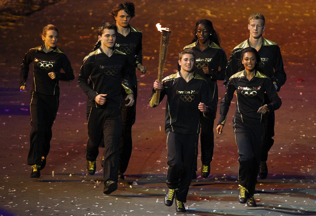 The Olympic torch is carried by seven young athletes towards the cauldron.