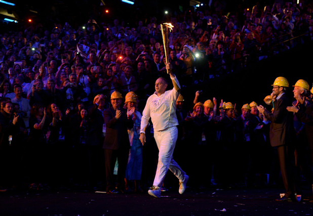 Sir Steve Redgrave carries the torch into the stadium.