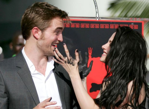 The couple having flirty fun at a hand and foot print ceremony