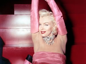 Marilyn Monroe in the now iconic pink gown and satin gloves.