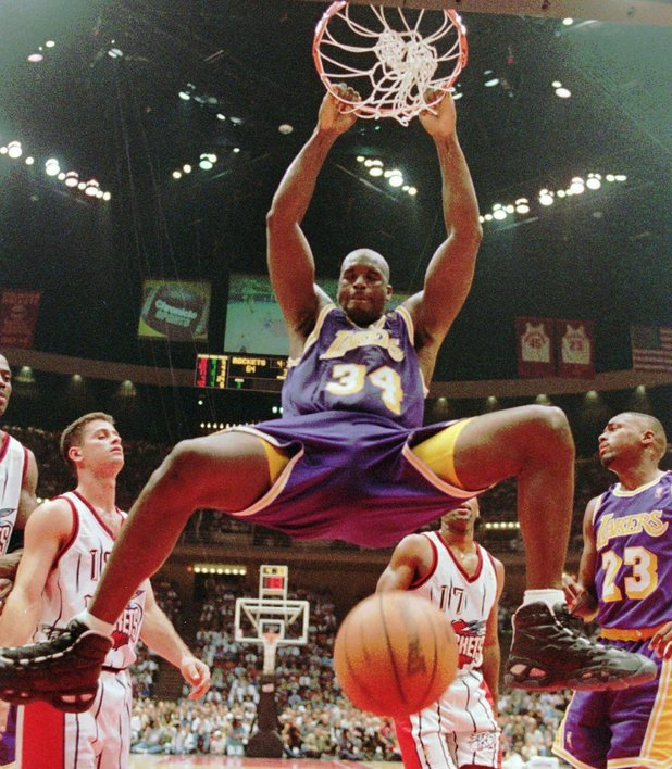 file photo shows Los Angeles Lakers' Shaquille O'Neal (34) hanging from the rim after a dunk during the third quarter against the Houston Rockets, in Houston.