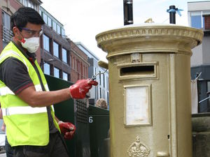 A red post box being painted gold in Barker&#39;s Pool, Sheffield, to honour Jessica Ennis and her gold medal heptathlon victory.