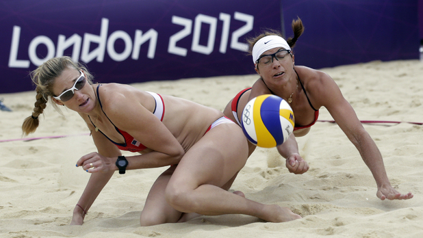 The United States's Misty May Treanor, right, dives over her teammate Kerri Walsh Jennings