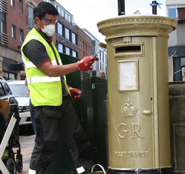 A red post box being painted gold in Barker's Pool, Sheffield, to honour Jessica Ennis and her gold medal heptathlon victory.