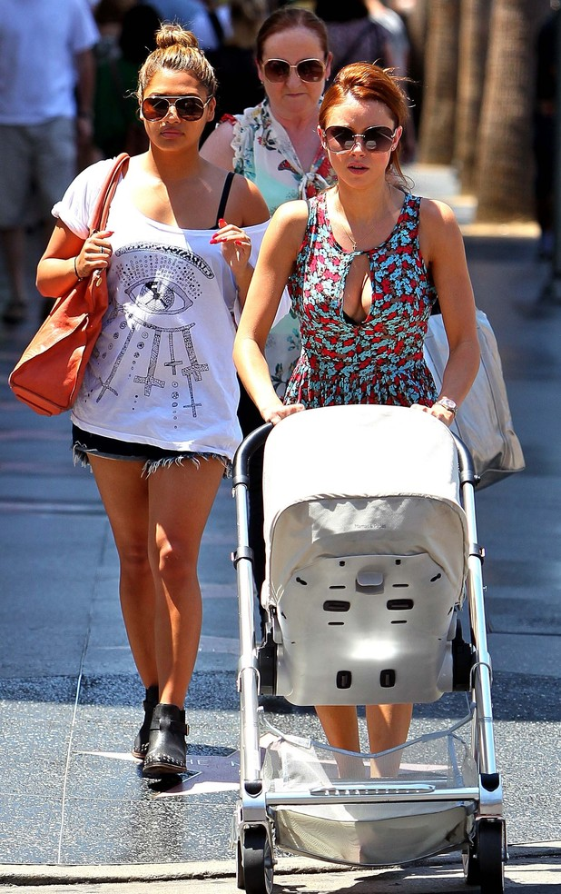 Une Healy takes her daughter for a stroll in California with Saturdays bandmate Vanessa White.