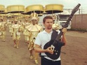 Matt Bellamy leads a crowd of golden drummers during preparations for the show.