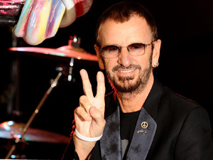 Ringo Starr, with his 'Knotted Gun' statue at the Gibson Guitar Studio, in central London, peace sign